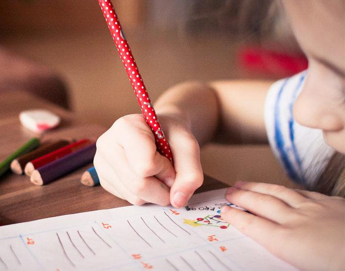 Mädchen schreibt mit Bleistift auf Papier